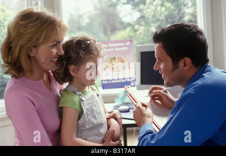 doctor talking to little girl and her mother - Stock Photo