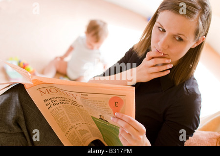 mother looking at worrying financial news in the paper with baby in the background - Stock Photo