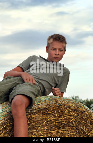13 years old boy on a Bale of Hay in Field in Summer - Stock Photo