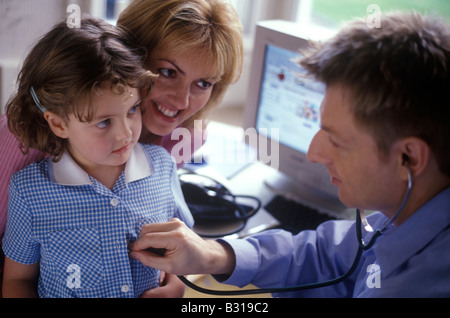 little girl with her mother with doctor listening to her chest - Stock Photo