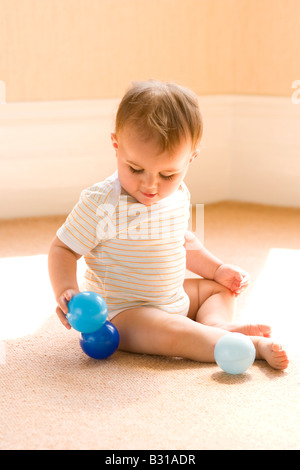 baby sitting up and playing with little balls - Stock Photo