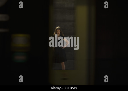 Young woman on opposite platform as train passes through - Stock Photo