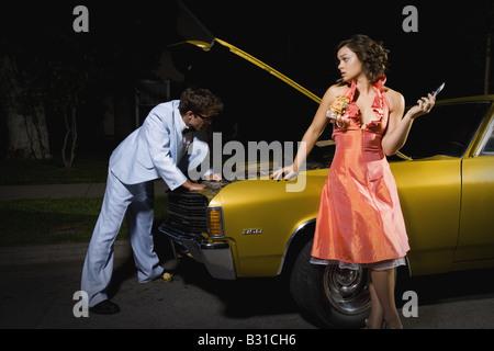 Prom couple checking broken down car - Stock Photo