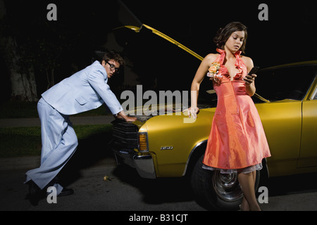 Prom couple with broken down car calling for help - Stock Photo