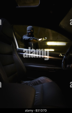 Interior view of thief breaking in car - Stock Photo