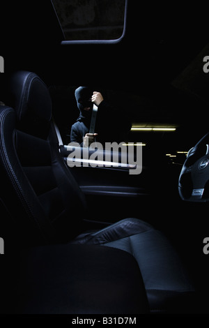 Thief breaking in car with Crowbar - Stock Photo