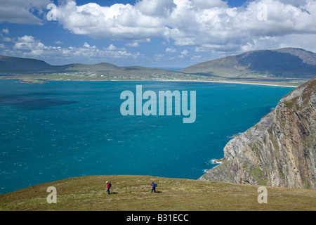 Hikers on the Menawn Cliffs, above Keel Bay. Achill Island, County Mayo, Ireland. - Stock Photo