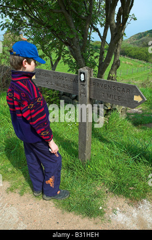 Child looking at a footpath signpost - Stock Photo
