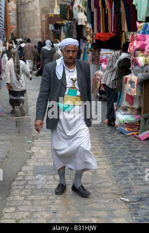 Yemeni man walking through the market in the Old City of Sanaa - Stock Photo