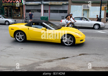 A late model yellow Corvette and a bicyclist on Hudson Street in Greenwich Village in New York - Stock Photo