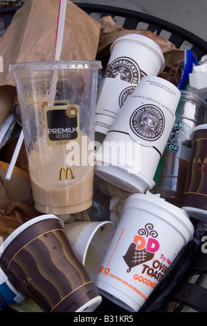 An overflowing trash can in New York filled with coffee cups from competing businesses - Stock Photo