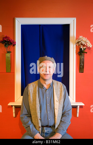 Man wearing hat sits on a bench next to a colorful wall. - Stock Photo