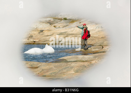 Looking through a hole in an iceberg at Ilulissat on Greenland with icebergs from the Jacobshavn icefjord behind - Stock Photo