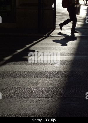 person's dark shadow on road surface in town - Stock Photo