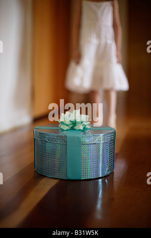 Five year old girl with green box wrapped in ribbon and rose - Stock Photo