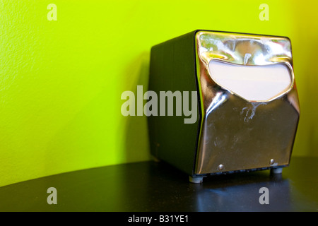 A paper napkin holder sits a table in a restaurant. - Stock Photo