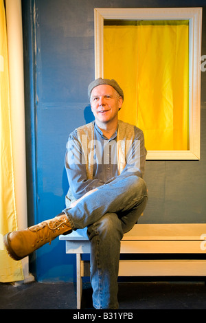 Man wearing hat sits on a bench next to a colorful wall - Stock Photo
