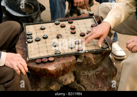 Close up of old male hands on a board game in Hanoi Vietnam played by two elderly Vietnamese men - Stock Photo