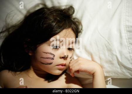 Five year old girl awakes with previous day s face paint She played a cat in a school production and didn t want - Stock Photo