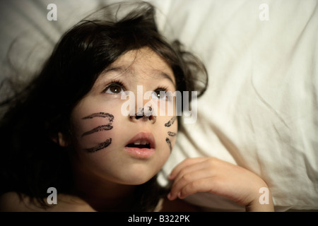 Five year old girl awakes with previous day's face paint. She played a cat in a school production and didn't want - Stock Photo