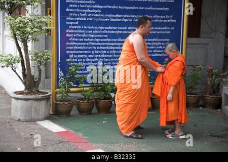 Monks at the base of Wat Saket located on Golden Mount in Bangkok, Thailand - Stock Photo