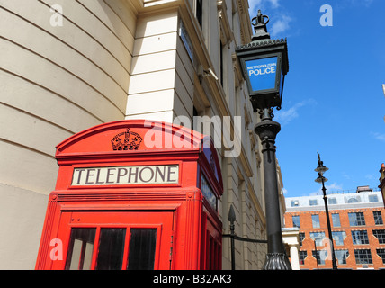 red telephone box and police sign London england call box communications help tourists law post lamp post call box - Stock Photo