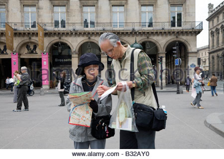 tourists reading a map at the Louvre Paris France Stock Photo