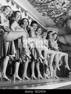 Chorus line of women with legs lifted - Stock Photo