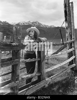 Woman leaning on wooden fence on ranch - Stock Photo