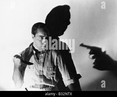 Man with knife at gunpoint - Stock Photo
