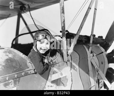 Little boy in cockpit of plane - Stock Photo