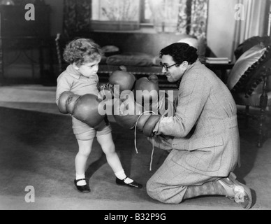 Father and young son playing with boxing gloves - Stock Photo