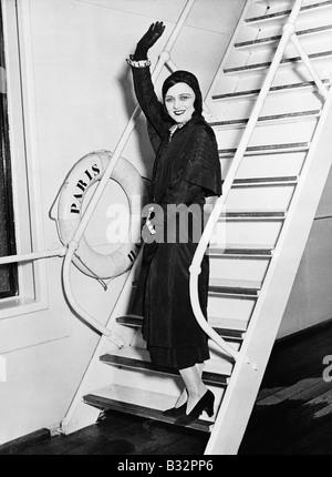 Female passenger on boat waving - Stock Photo