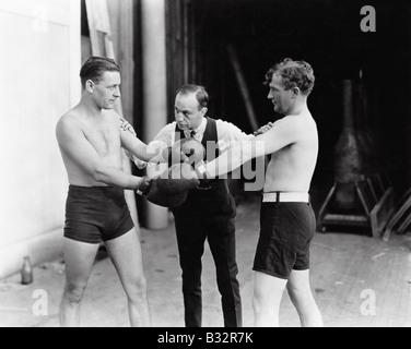 Two boxers and a referee - Stock Photo