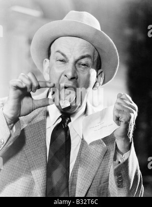 Man with a postage stamp stuck on his tongue - Stock Photo
