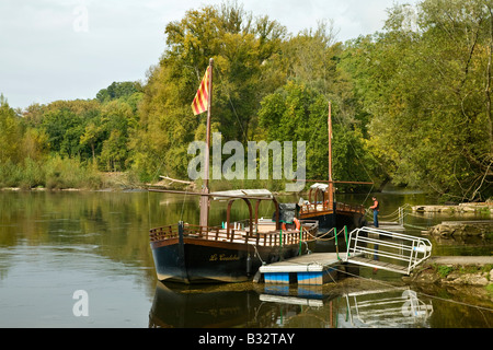 A traditional Gabarre on the Dordogne River at Beynac. Beside the jetty for tourist excursions. France, EU. - Stock Photo