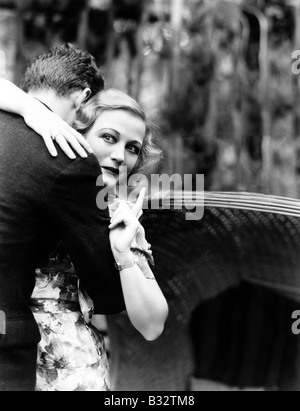 Young woman embracing man pointing towards information board - Stock Photo