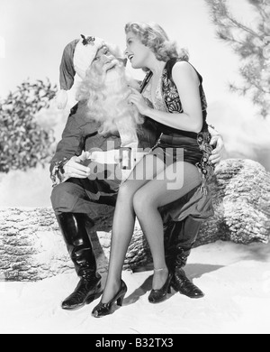 Woman and Santa Claus sitting together laughing - Stock Photo