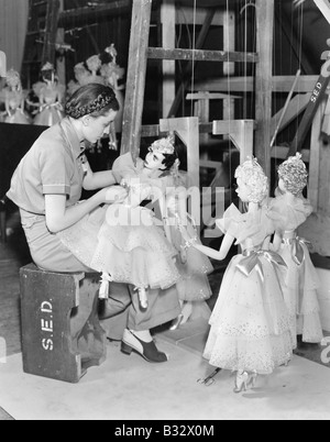 Young woman working with puppets on a string - Stock Photo