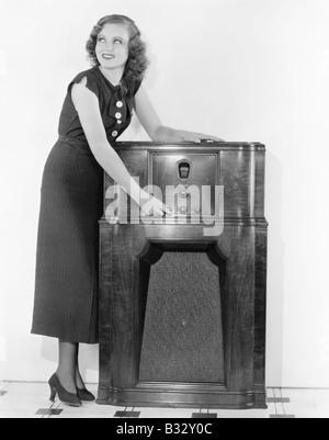 Woman next to a radio turning the knobs - Stock Photo