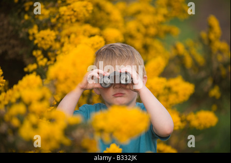 Toddler 3 Yr old boy bird watching on heath Norfolk April - Stock Photo