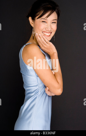 A young asian woman smiles as she rests her chin on hand - Stock Photo