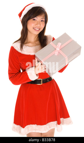 A cute asian girl in a santa costume has a big present wrapped in silver paper - Stock Photo