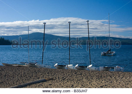 A catamaran anchored on the blue waters of Lake Coeur d Alene Idaho with smaller rentals on the beach - Stock Photo