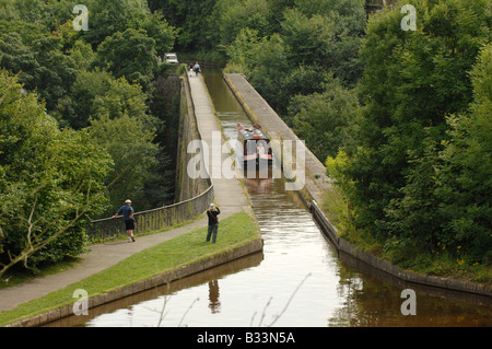 A narrowboat crossing the Chirk Aqueduct on Llangollen Canal which bridges the border between England and Wales - Stock Photo