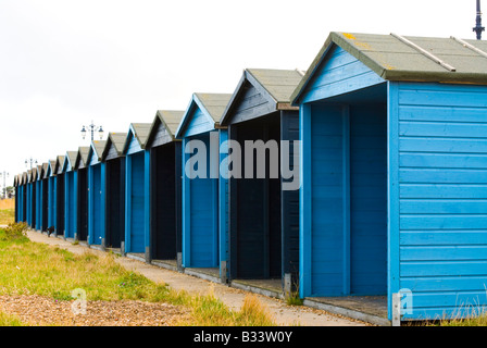 a row of wooden beach huts in southsea, portsmouth, painted blue. - Stock Photo