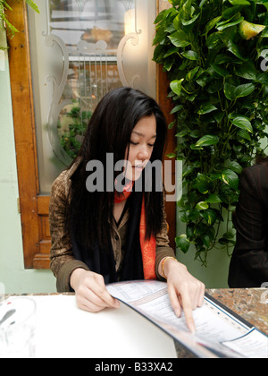 A young Asian woman point to the items she want to order from a menu in a restaurant - Stock Photo