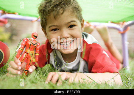 Boy plays with his Power Ranger in the Garden. - Stock Photo