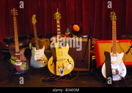 various electric guitars on stage, including a renowned Gibson ES295 reissue - Stock Photo