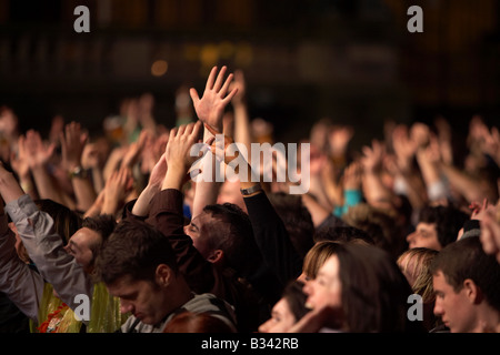 hands waving and pointing in a crowd of people during a nighttime concert in Belfast - Stock Photo